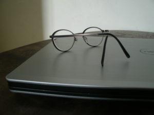 Laptop und Brille auf Tisch